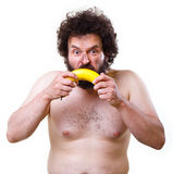 Caveman with a banana. Wild, undressed man with crazy hair and beard, holding a banana in his hands Stock Photos