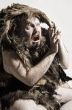 Caveman in bear skin. Isolated on white stock photography