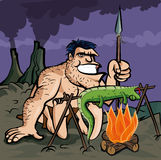Caveman cooking a lizard Stock Photo