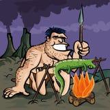 Caveman cooking a lizard Stock Photo