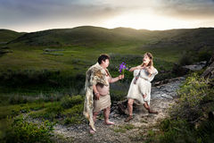 Caveman couple in love at mountains. Primitive caveman dressed in animal skin giving flowers to happy cave women in the mountains stock photo