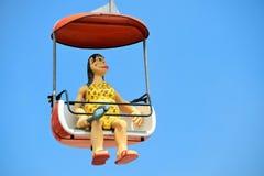 Caveman Lady Rides Gondola at Santa Cruz Beach Boardwalk. A caveman woman, with club in hand, enjoys a day at the amusement park in Santa Cruz, California Stock Photos