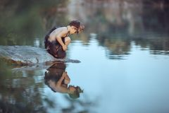 Caveman. Little boy sitting on the beach and looks at the water. Caveman boy sitting on the rock and looking at him self in the water reflection in lake stock image
