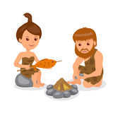Caveman. Male kindles fire. Female cook the fish on the fire. Stock Photos