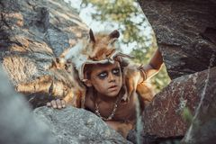 Caveman, manly boy hunting outdoors. Ancient warrior portrait. Caveman, manly boy hunting outdoors. Prehistoric tribal boy outdoors on nature. Young shaggy and royalty free stock photography