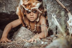 Caveman, manly boy hunting outdoors. Ancient warrior portrait. Caveman, manly boy hunting outdoors. Prehistoric tribal boy outdoors on nature. Young shaggy and royalty free stock image