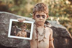 Caveman, manly boy making holding tablet PC. Caveman, manly boy holding tablet PC with his photo on screen. Funny young primitive boy outdoors. Evolution royalty free stock photo