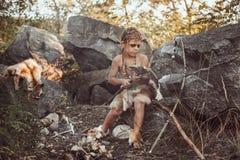 Caveman, manly boy making primitive stone weapon in camp. Caveman, manly boy making primitive stone weapon. Funny young primitive boy outdoors near bonfire royalty free stock image