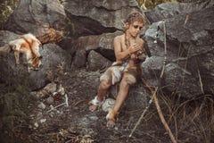 Caveman, manly boy making primitive stone weapon in camp. Caveman, manly boy making primitive stone weapon. Funny young primitive boy outdoors near bonfire stock photo