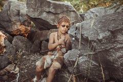 Caveman, manly boy making primitive stone weapon in camp. Caveman, manly boy making primitive stone weapon. Funny young primitive boy outdoors near bonfire stock photography