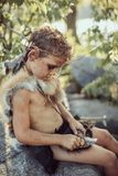 Caveman, manly boy making primitive stone weapon in camp. Caveman, manly boy making stone axe. Funny young primitive boy outdoors crafting weapon. Evolution stock photo