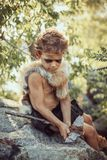 Caveman, manly boy making primitive stone weapon in camp. Caveman, manly boy making stone axe. Funny young primitive boy outdoors crafting weapon. Evolution stock images