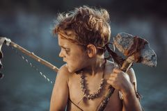 Caveman, manly boy with primitive weapon hunting outdoors. Ancient prehistoric warrior. Heroic movie look. Angry caveman, manly boy with stone axe and bow stock photos