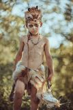 Caveman, manly boy with primitive weapon outdoors. Ancient prehistoric warrior. Angry caveman, manly boy with stone axe and animal skull. Prehistoric tribal boy stock photo