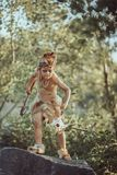Caveman, manly boy with primitive weapon outdoors. Ancient prehistoric warrior. Angry caveman, manly boy with stone axe and animal skull. Prehistoric tribal boy royalty free stock photography