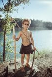 Caveman, manly boy with stone axe and bow hunting outdoors. Caveman, manly boy with stone axe and bow hunting near river. Prehistoric tribal boy outdoors on royalty free stock photography
