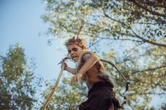 Caveman, manly boy with weapon. Aggressively shouting. Dramatic action photo of young primitive boy outdoors in forest. Evolution survival concept. Calm boy royalty free stock image