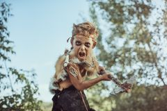 Caveman, manly boy with weapon. Aggressively shouting. Dramatic action photo of young primitive boy outdoors . Evolution survival concept. Calm boy outside stock images