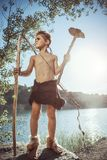 Caveman, manly boy with stone axe and bow hunting. Caveman, manly man with stone axe and bow hunting near river. Prehistoric tribal boy outdoors on nature. Young stock photos