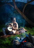 Caveman playing drum. Caveman dressed in wolf skin playing drum near bonfire in the forest stock images