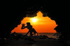 Caveman posture or action in the cave at sunset. Caveman posture or action in the cave at red sky sunset background stock images