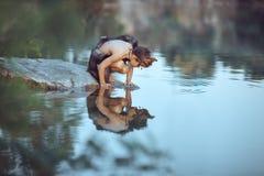 caveman Rapaz pequeno que senta-se na praia e nos olhares na água foto de stock