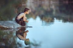 caveman Rapaz pequeno que senta-se na praia e nos olhares na água fotografia de stock royalty free