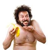 Caveman som är lycklig om att ha en banan som ska ätas Royaltyfri Foto