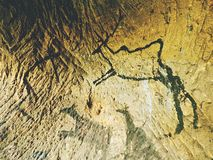 Caveman symbols on sandstone wall. Paint of human hunting,  prehistoric picture. Stock Images