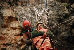 Caver abseiling in a pothole. A portrait of a young female caver exploring the cave stock images