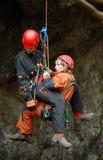 Caver che si cala in corda doppia in una buca Fotografia Stock