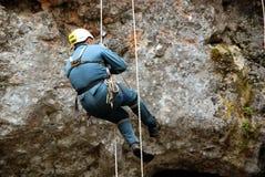 Caver che si cala in corda doppia in una buca Fotografia Stock Libera da Diritti