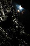 Caver desciende en una cueva Foto de archivo libre de regalías