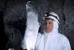 Caver explores ice stalagmite. Speleologist in a cave examines a giant ice stalagmite covered with hoarfrost, against a background of a dark rock covered with stock photos