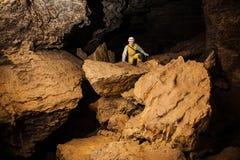 Caver fêmea novo que explora a caverna Fotografia de Stock Royalty Free