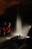 Caver mit einem kleinen Wasserfall Stockbild