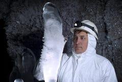 Caver onderzoekt ijsstalagmiet stock foto's