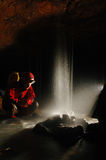 Caver with a small waterfall Stock Image