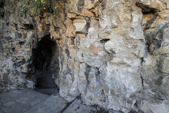 Cavern entrance, gray rocks background. Royalty Free Stock Images