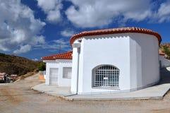 Caverna-casa branca e céu azul com nuvens fotografia de stock
