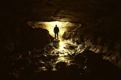 Caverna com silhueta e água do homem Imagens de Stock Royalty Free