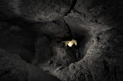 Caverne au fond avec l'homme à l'entrée Photographie stock libre de droits