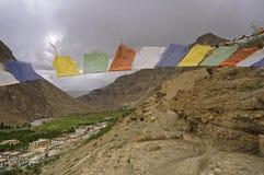 Caverne e bandiere buddisti antiche di preghiera nel deserto ad alta altitudine della montagna Fotografia Stock