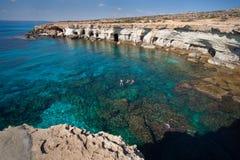 Cavernes de mer de la Chypre. Père avec le bain de deux fils. Photographie stock