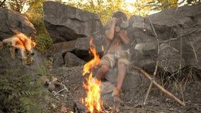Cavernicolo, ragazzo virile che fa arma di pietra primitiva nel campo archivi video