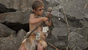 Cavernicolo, ragazzo virile che fa arma di pietra primitiva nel campo stock footage