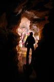 Cavers que explora una galería en una cueva Imagen de archivo