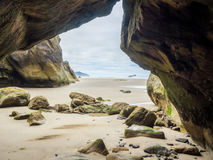 Caves in the cliff at a sandy beach Royalty Free Stock Images