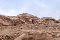 Caves in the rock near the road leading to Petra - the capital of the Nabatean kingdom in Wadi Musa city in Jordan. Wadi Musa, Jordan, December 06, 2018 : Caves royalty free stock photos