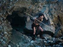 Cavewoman, die mit Stange jagen Stockbild